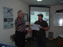 Instructor Dennis Mathis presents BJ Finney with his EOC certificate.
