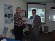Instructor Dennis Mathis presents Brett Pelham with his EOC certificate.